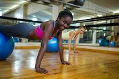 Portrait of smiling woman doing pilates exercises on fitness ball with coach in fitness studio poster