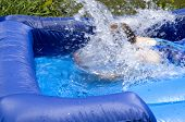 picture of inflatable slide  - Woman causing splash while landing on water slide - JPG
