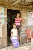 stock photo of tooth gap  - mother with diastema gap-tooth and daughter in front of clapboard house in poverty of Big Corn Island Nicaragua Central America  ** Note: Slight blurriness, best at smaller sizes  - JPG
