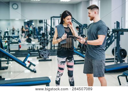 poster of Fitness Woman Exercising With Fitness Trainer In Gym. Personal Fitness Instructor. Personal Training