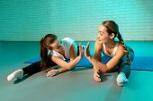 Beautiful Two Young Slim Gymnast Women In Sports Clothing Stretching On The Floor On Fitness Mat In  poster