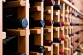 stock photo of racks  - Wine cellar with bottles stacked in wooden rack.