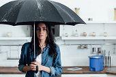 Amazed Woman Standing Under Umbrella During Leak In Kitchen poster