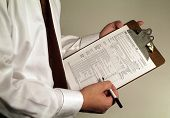 stock photo of lien  - man in suit holding tax form on clipboard ready to fill it out - JPG