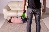 Domestic Violence, Alcoholic And Abuse Concept - Drunk Man With Bottle Abusing His Wife Lying On The poster