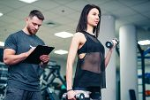 Fitness Woman Exercising With Fitness Trainer In Gym. Personal Fitness Instructor. Personal Training poster
