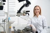 Charming Woman Working As Stomatologist, Posing At Workplace. Beautiful Female Dentist Sitting, Lean poster