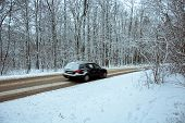 Car Quickly Driving Through The Woods To The Asphalt Road Covered With Snow - A Fuzzy View Of The Ca poster