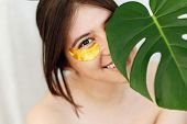 Portrait Of Beautiful Young Woman With Golden Eye Patches At Green Monstera Leaf On White. Happy Gir poster