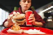Young Man Dishes Fast Food At A Fast Food Restaurant. Man Holds A Burger In His Hand, Drinking A Col poster