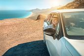 Happiness mother and son, sitting in white car and look on the beautiful ocean coastline with mounta poster