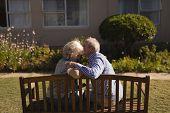 Rear view of active senior Caucasian man kissing senior Caucasian woman in the park poster