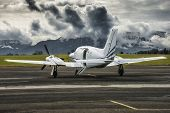 Propeller Plane Parked At The Airport. Mountain Airport. Airport In Front Of High Mountains. poster