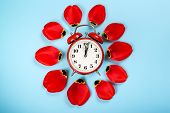Alarm Clock With Tulip Petals Around. Flat Lay Style, Over Blue Background. Daylight Savings Time Co poster