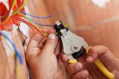 picture of electrician  - Electrician peeling off insulation from wires  - JPG