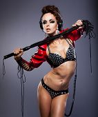 image of sadistic  - young sexy woman in headphones and whip in erotic pose - JPG