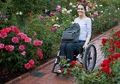 stock photo of disabled person  - Beautiful young woman in a wheelchair visiting a rose garden in Oregon - JPG