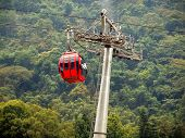 stock photo of ropeway  - The red gondola of a ropeway travells past a misty forest - JPG
