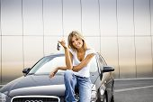 stock photo of car key  - Young woman holding keys to new car - JPG