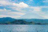 stock photo of gunung  - Gunung Agung the highest volcano on Bali island Indonesia with blue cloudy sky and sea on front - JPG