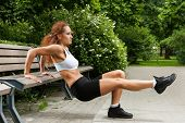 Muscled fitness girl is working out in the park near the bench