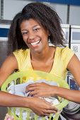 Portrait of happy young woman with laundry basket at laundromat
