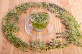 image of crown green bowls  - Wreath from thyme flowers and herbal tea on a wood table background - JPG