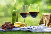 stock photo of grape  - Picnic setting with red wine glasses bottle and picnic hamper basket - JPG