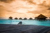 stock photo of pacific islands  - Over water bungalows with steps into amazing green lagoon - JPG