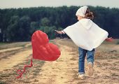 stock photo of balloon  - Lovely little girl playing with red heart shaped balloon - JPG