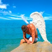 image of sinner  - Muscular man with angel wings on the beach - JPG