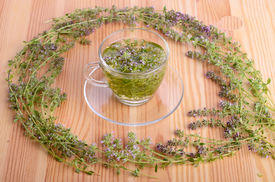 stock photo of crown green bowls  - Wreath from thyme flowers and herbal tea on a wood table background - JPG