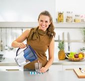 foto of pitcher  - Happy young housewife pouring water into glass from water filter pitcher
