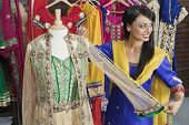 image of dupatta  - Indian female dressmaker measuring traditional outfit at design studio - JPG