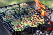foto of marrow  - Cooking of vegetable marrow on barbecue grill at picnic - JPG