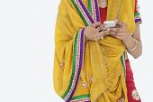 stock photo of salwar  - Midsection of woman in Indian clothing using cell phone over gray background - JPG