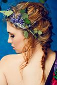 stock photo of crown  - portrait of a beautiful woman with red hair in curly braided hairstyle wearing a crown of fresh flowers - JPG