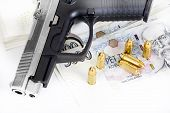 stock photo of bullet  - detail of gun with bullet on czech banknotes background - JPG