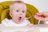 pic of child feeding  - Mother feeds the child with a spoon - JPG