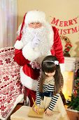 stock photo of letters to santa claus  - Little cute girl writing letter to Santa Claus near Christmas tree at home - JPG