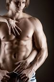 pic of undressing  - Sexy muscular naked man and female hands unbuckle his jeans on a dark background - JPG
