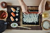stock photo of sushi  - hands cooking sushi with rice salmon and nori - JPG