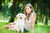 picture of golden retriever puppy  - Young woman playing with her golden retriever puppy outdoors - JPG