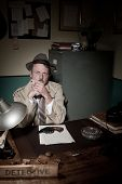 pic of 1950s style  - Confident detective smoking at desk in trench coat 1950s film noir style - JPG