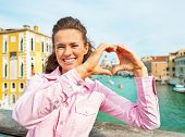 foto of piccolo  - Happy young woman showing heart shaped hands framing santa maria della salute venice italy - JPG