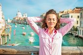 stock photo of piccolo  - Relaxed young woman standing on bridge with grand canal view in venice italy - JPG