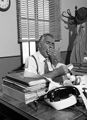 picture of yawn  - Tired accountant yawning and checking bills at his desk vintage office - JPG