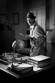 picture of 1950s style  - Attractive detective pointing a gun next to a desk 1950s style office - JPG