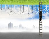 picture of turbines  - businessman climb on ladder between two inverted world with pollution cityscape and clean natural sky grass wind turbines environmental protection and alternative energy concept - JPG
