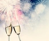 foto of congrats  - Toasting with two champagne glasses against fireworks and holiday lights - JPG